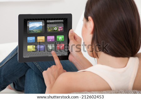 Rear view of young woman using various applications on digital tablet at home - stock photo