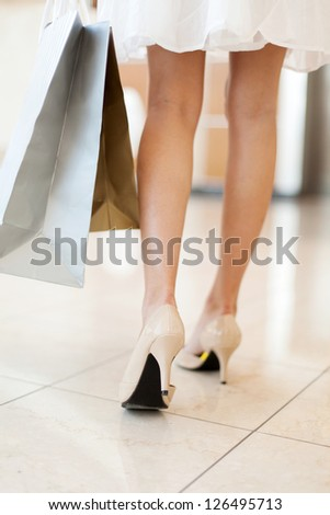 rear view of young woman walking with shopping bags - stock photo