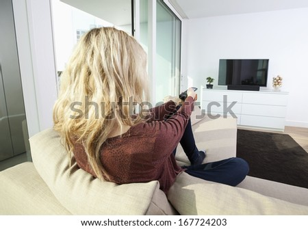 Rear view of young woman watching television on sofa at home - stock photo