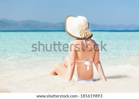 Rear view of young woman wearing sunhat while enjoying ocean view at beach - stock photo