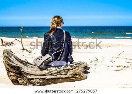 Rear view of young woman with blond hair, young woman relaxing on the beach vacation enjoying ocean view sitting on wood, wearing black leather jacket - stock photo