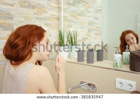 Rear View of Young Woman with Red Hair Brushing Teeth with Eyes Closed and Reflection in Luxury Bathroom Mirror, as part of Morning Hygiene Routine - stock photo