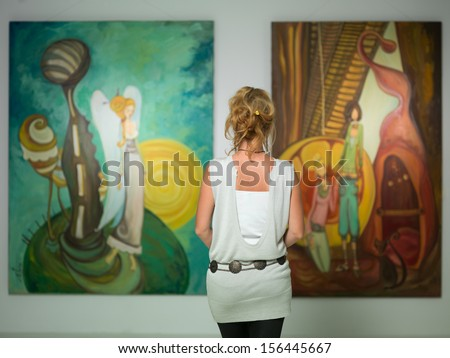 rear view of younga caucasian woman stading in an art gallery in front of two large colorful paintings - stock photo