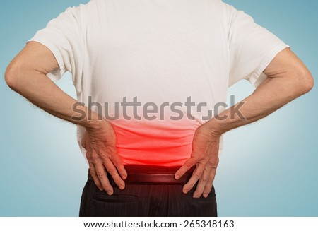 rear view old man grandpa holding his painful lower back colored in red with hands isolated on light blue  background. Human health problems   - stock photo