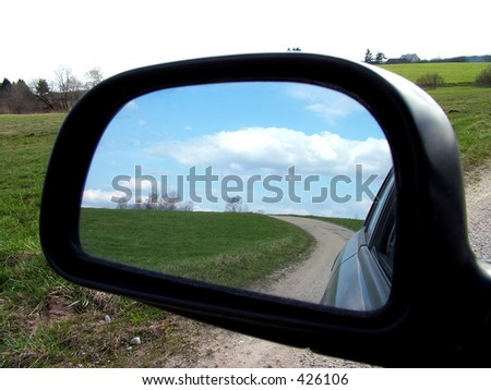 Rear view on a car mirror, road to hill - stock photo