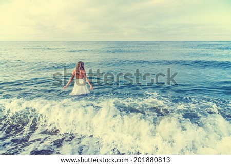 Rear view on a single lady going into the sea. Horizontal photo - stock photo