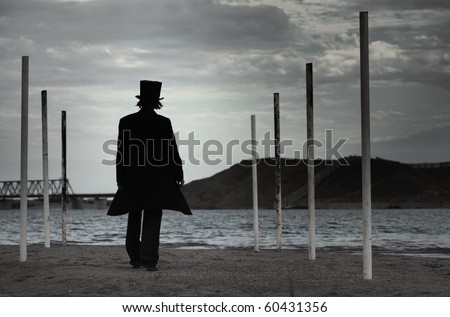 Rear view on alone man in the black coat and top-hat going to the sea. Natural darkness. Artistic colors added - stock photo