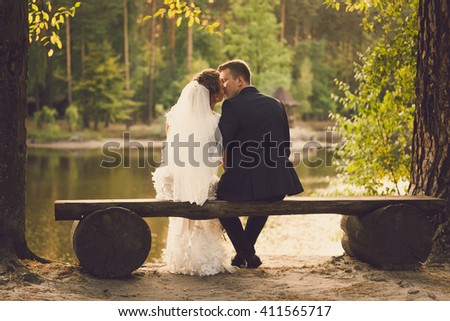 Rear view on beautiful newlyweds kissing on bench at river - stock photo
