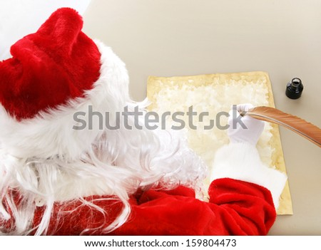 Rear view over Santa Claus' shoulder as he's writing his Christmas list.  Room for your text.   - stock photo