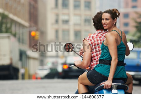 Rear view portrait of a couple riding on moped in street - stock photo