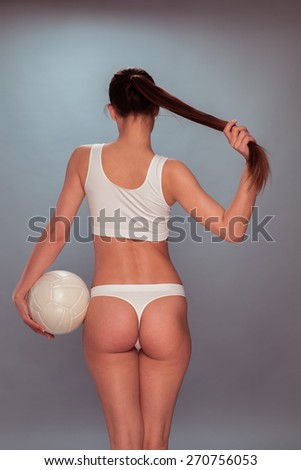 Rear View Portrait of a Sexy Woman, Wearing White Underwear, Holding her Long Hair and a Volleyball Ball on a Gray Background. - stock photo
