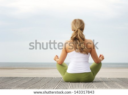 Rear view portrait of a young woman sitting at beach in yoga pose - stock photo