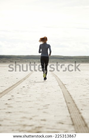 Rear view portrait young woman running at the beach - stock photo
