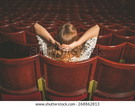 Rear view shot of a young woman sitting alone in an auditorium - stock photo