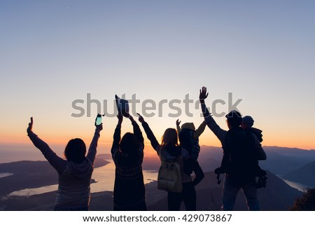 Rear view shot of group of young people standing on top of a mountain and enjoying the view of sunset - stock photo