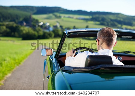 Rear view shot of man driving a convertible car outdoors - stock photo