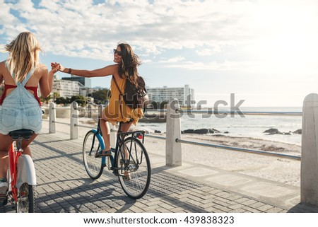 Rear view shot of two young woman holding hands and riding bicycles on a seaside promenade. - stock photo