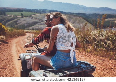Rear view shot of young couple riding on a quad bike in countryside and looking away smiling. Woman sitting behind her boyfriend driving an quad on country road. - stock photo