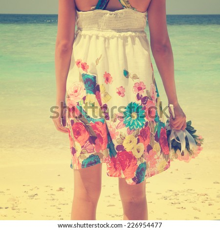Rear view single girl standing alone at beach, hand holding flower bouquet in vintage toned. - stock photo