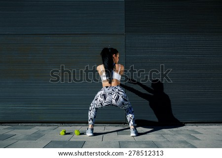 Rear view sporty woman with perfect figure and buttocks doing squats against wall with copy space for your text message,fit female in sportswear squatting after training on black background outdoors - stock photo