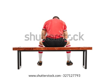 Rear view studio shot of a sad male football player sitting on a wooden bench and looking down isolated on white background - stock photo