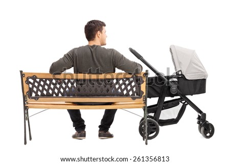 Rear view studio shot of a young father sitting on bench with baby stroller beside him isolated on white background - stock photo