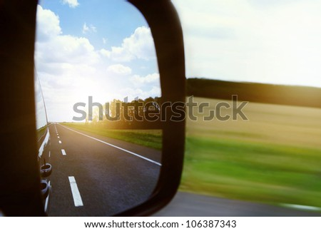 Rearview Mirror View on the Hightway and Blue Sky , Clouds and morning Sun - stock photo