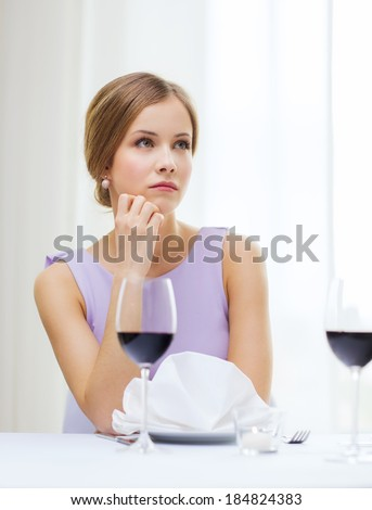 reastaurant and happiness concept - upset young woman with glass of red whine waiting for date at restaurant - stock photo