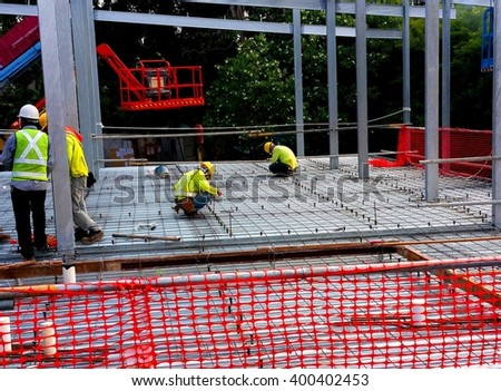 Rebars are laid. Shear studs are welded to the top flange of the steel section through metal deck. Workers are installing the threaded rods which are used with metal strut to suspend from ceiling. - stock photo