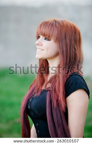 Rebellious teenager girl with red hair smiling - stock photo