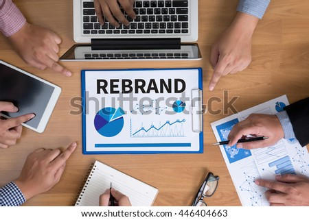 REBRAND Change Identity Branding Business team hands at work with financial reports and a laptop, top view - stock photo
