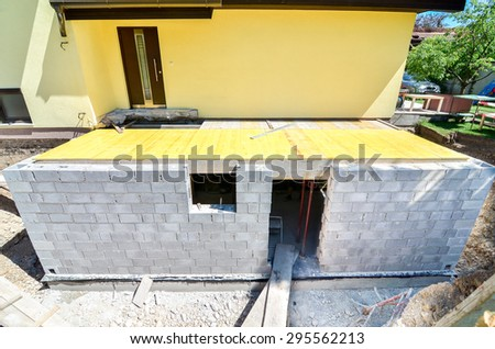 Rebuilding a family house and adding an  extension, building walls with space for windows and doors. Construction tools - stock photo