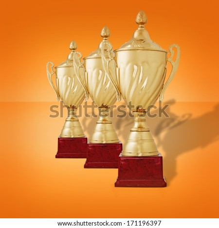 Receding row of gold trophy cups with lids on wooden plinths waiting to be awarded to the winners of a championship or competition on an orange background - stock photo