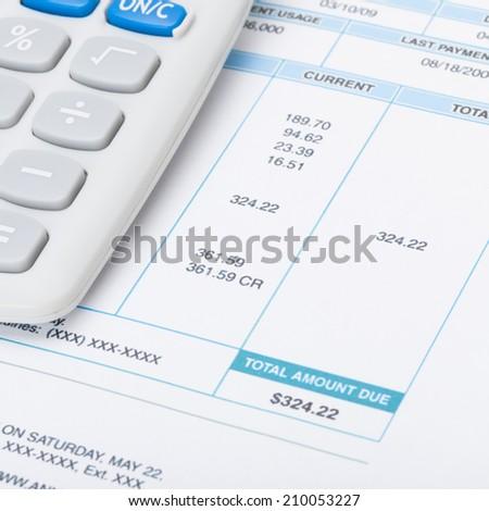 Receipt next to calculator over it - studio shot - 1 to 1 ratio - stock photo