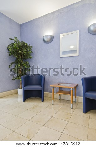 reception area with blue armchairs and plant - stock photo