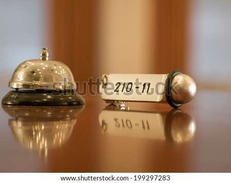 Reception - Hotel bell and key lying on the desk - stock photo