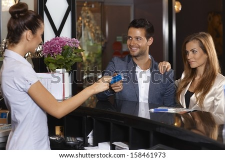 Receptionist giving key card to new guests at hotel, smiling happy. - stock photo