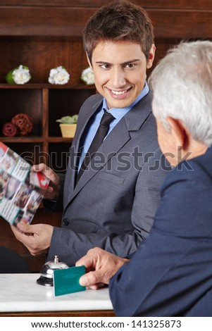 Receptionist in hotel giving brochure to senior guest - stock photo