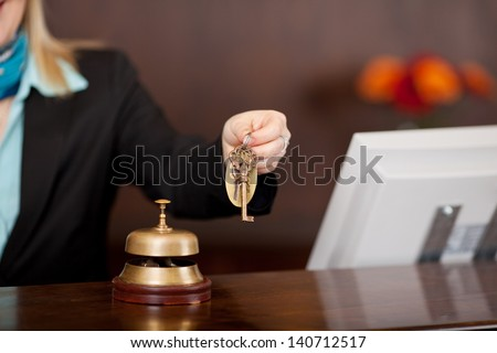 receptionist passing room keys over the counter - stock photo