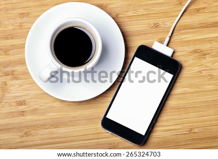 Rechargeable smartphone and a cup of espresso - stock photo