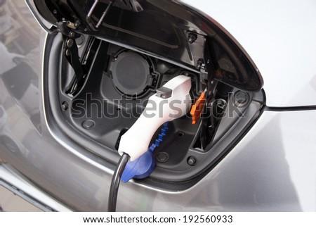 Recharging an electric car / electric car - stock photo