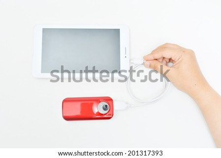 Recharging smart phone tablet from power bank, electricity's source portable.  - stock photo