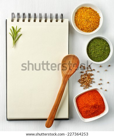 Recipe book and various spices on white wooden background - stock photo
