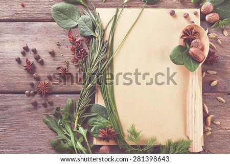 Recipe book page with spoon and different herbs on wooden background - stock photo