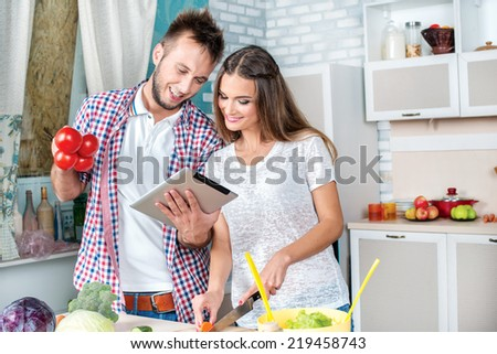 Recipe for cooking tomatoes. Young and beautiful couple in love food prepared according to the recipe on the tablet while they are preparing breakfast in the kitchen. - stock photo