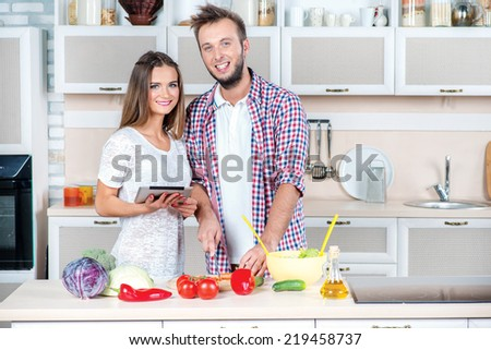 Recipe for healthy cooking. Young and beautiful couple in love food prepared according to the recipe on the tablet while they are preparing breakfast in the kitchen - stock photo