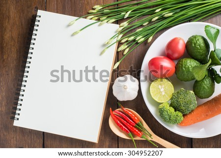 Recipe notebook, tomatoes, Red chilli, garlic and lemon on wood texture background - stock photo