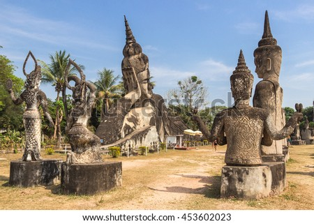 Reclining Buddha ancient statue among hindu and buddhism gods sculptures in front in Buddha park, Vientiane, Laos - stock photo