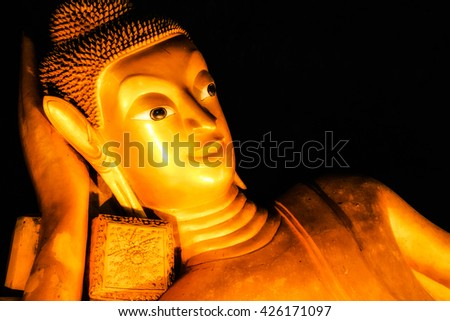 Reclining Buddha gold statue face in black background - stock photo