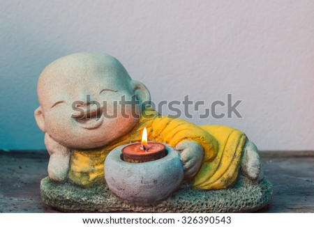 reclining Buddha smile  and candle - stock photo